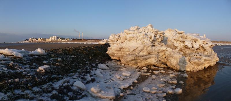 Aufgetürmte Eisschollen, im Hintergrund Häuser am Weststrand